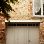 Hardwood framed ledge and brace garage doors painted in white. Manufactured and installed by James Riggall Fine Joinery, Exeter