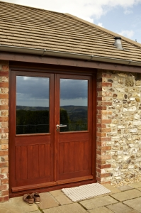 Half glazed doors with framed tongue and groove bboarding on the bottom half. Manufacture using solid Oak by James Riggall Fine Joinery, Devon